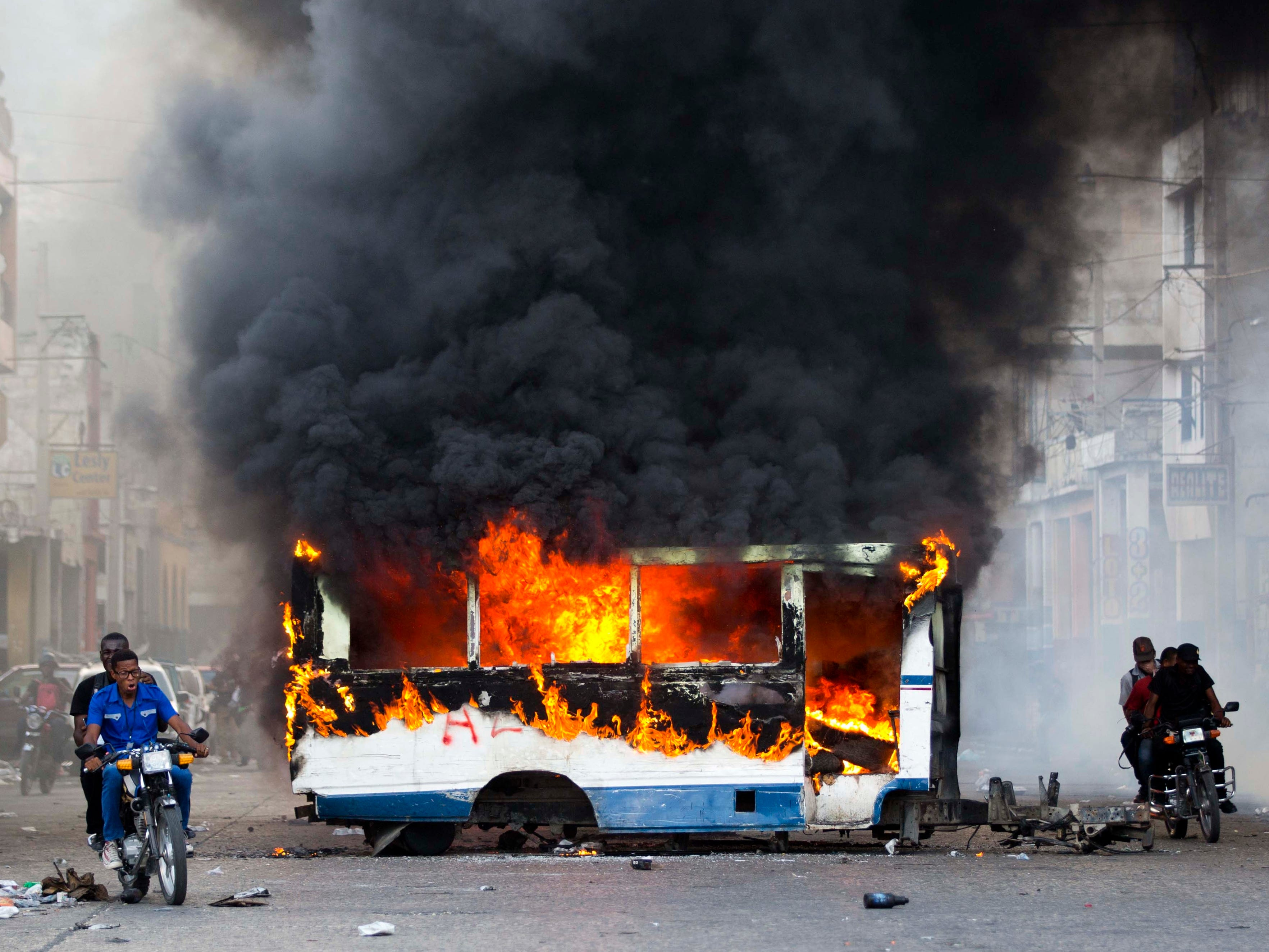 Motorcyclists pass a burning bus, set fire by opposition protesters demanding to know how Petro Caribe funds have been used by the current and past administrations, on the sidelines of events marking the 215th anniversary of independence Battle of Vertieres in Port-au-Prince, Haiti, Sunday, Nov. 18, 2018. Much of the financial support to help Haiti rebuild after the 2010 earthquake comes from Venezuela's Petro Caribe fund, a 2005 pact that gives suppliers below-market financing for oil and is under the control of the central government.