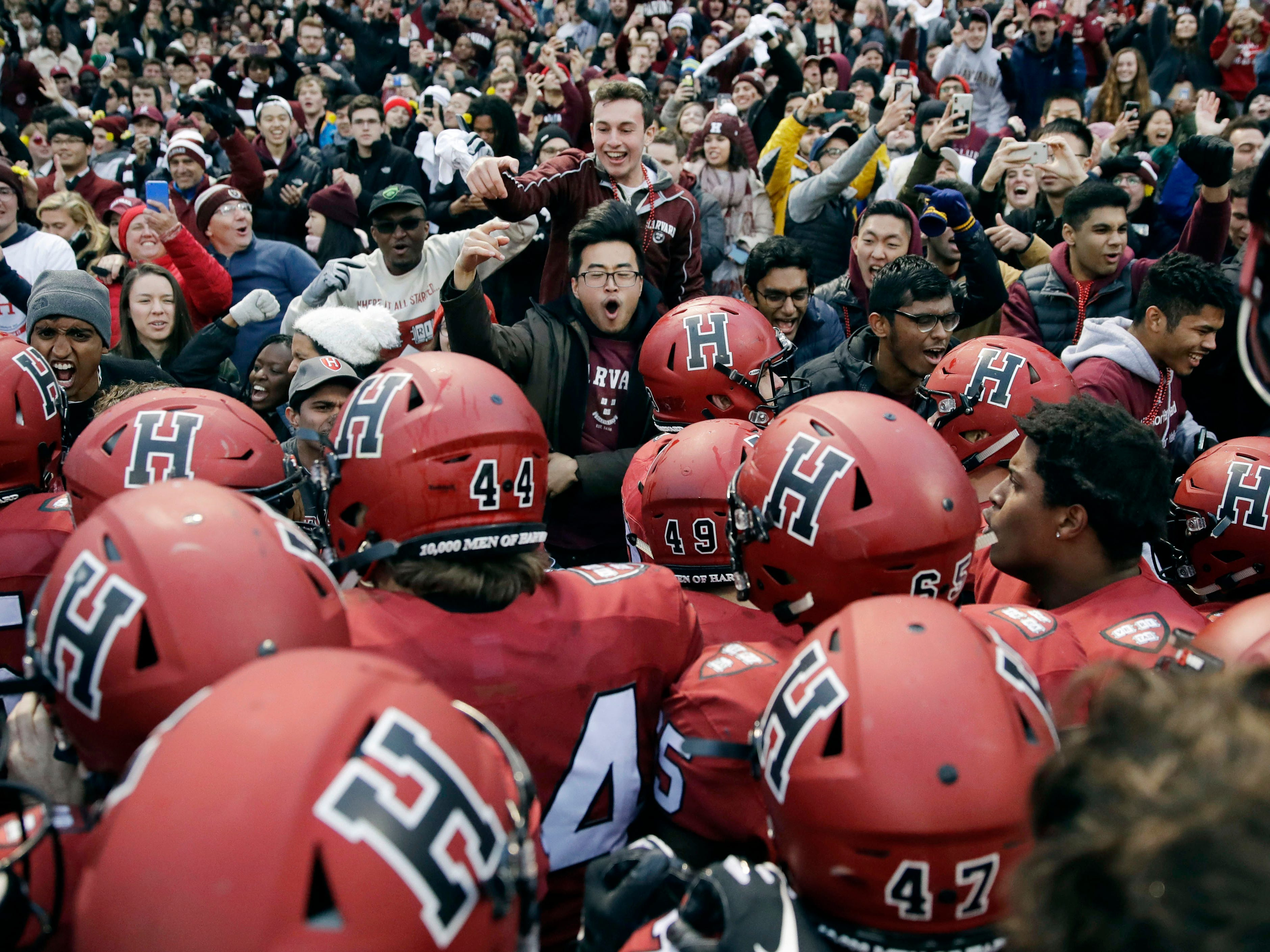 Harvard players, students and fans celebrate a win over Yale after an NCAA college football game at Fenway Park in Boston, Saturday, Nov. 17, 2018. Harvard defeated Yale 45-27.