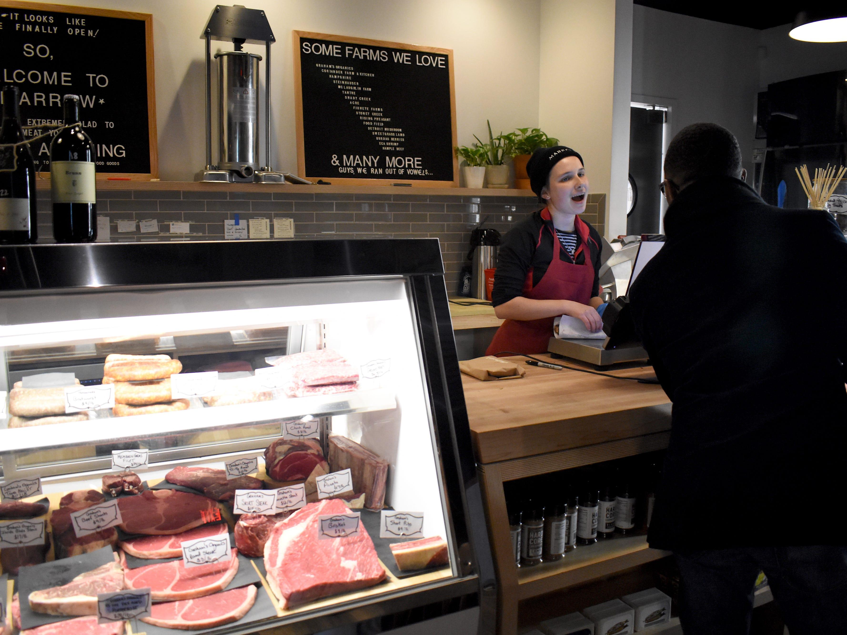 Butcher Mara Steinitz, left, helps customer Jason Hill, of Detroit.