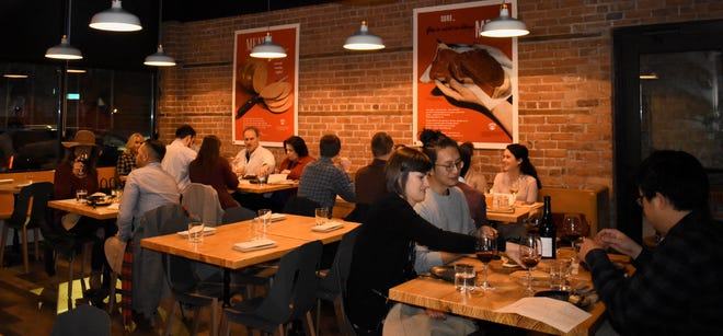 Diners settle in behind bare wood tables in the seductively-lit eatery. 