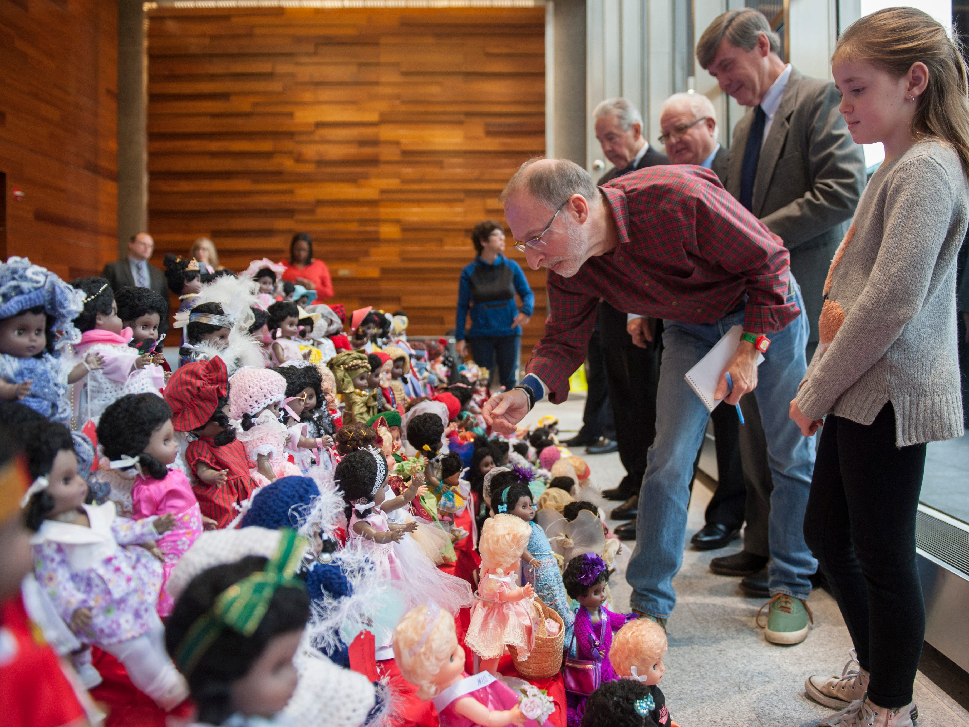 Neal Rubin of The Detroit News leans in for a closer look at the dolls as he and fellow judge Emily Stanczak, 9, of Auburn Hills consider their choices from an array of fancifully dressed dolls.