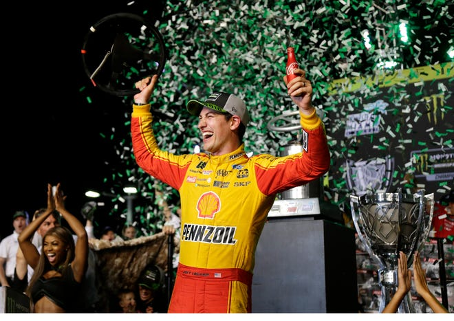 Joey Logano holds his steering wheel after winning the NASCAR Cup Series Championship auto race Sunday at the Homestead-Miami Speedway.