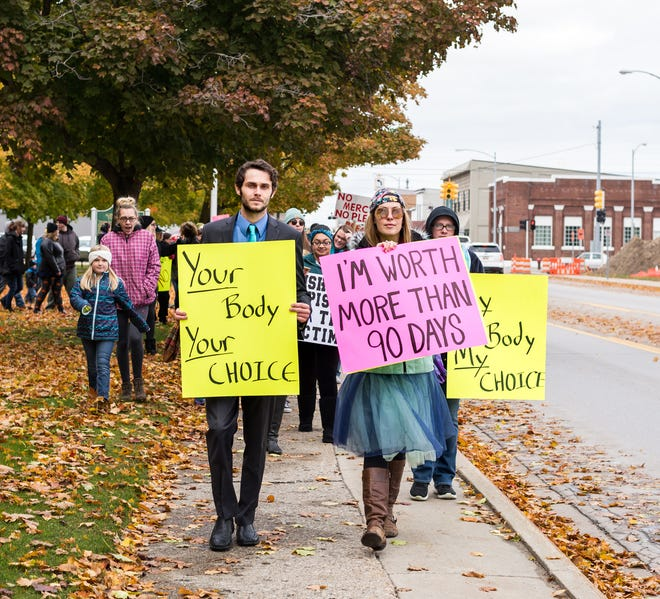 Event organizers Brett Heise and Brittany Szatkowski lead a group of about 60 demonstrators from Alpena City Hall on October 20.  They protested the light sentence of local athlete Tommy Hein, who got 90 days in jail after pleading guilty to felonious assault in a case where a local woman was allegedly raped by three local athletes.