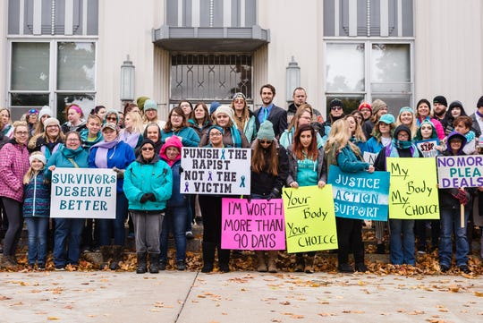 Demonstrators gather on steps of Alpena City Hall in October to protest light sentencing in rape cases and to support rape victims.