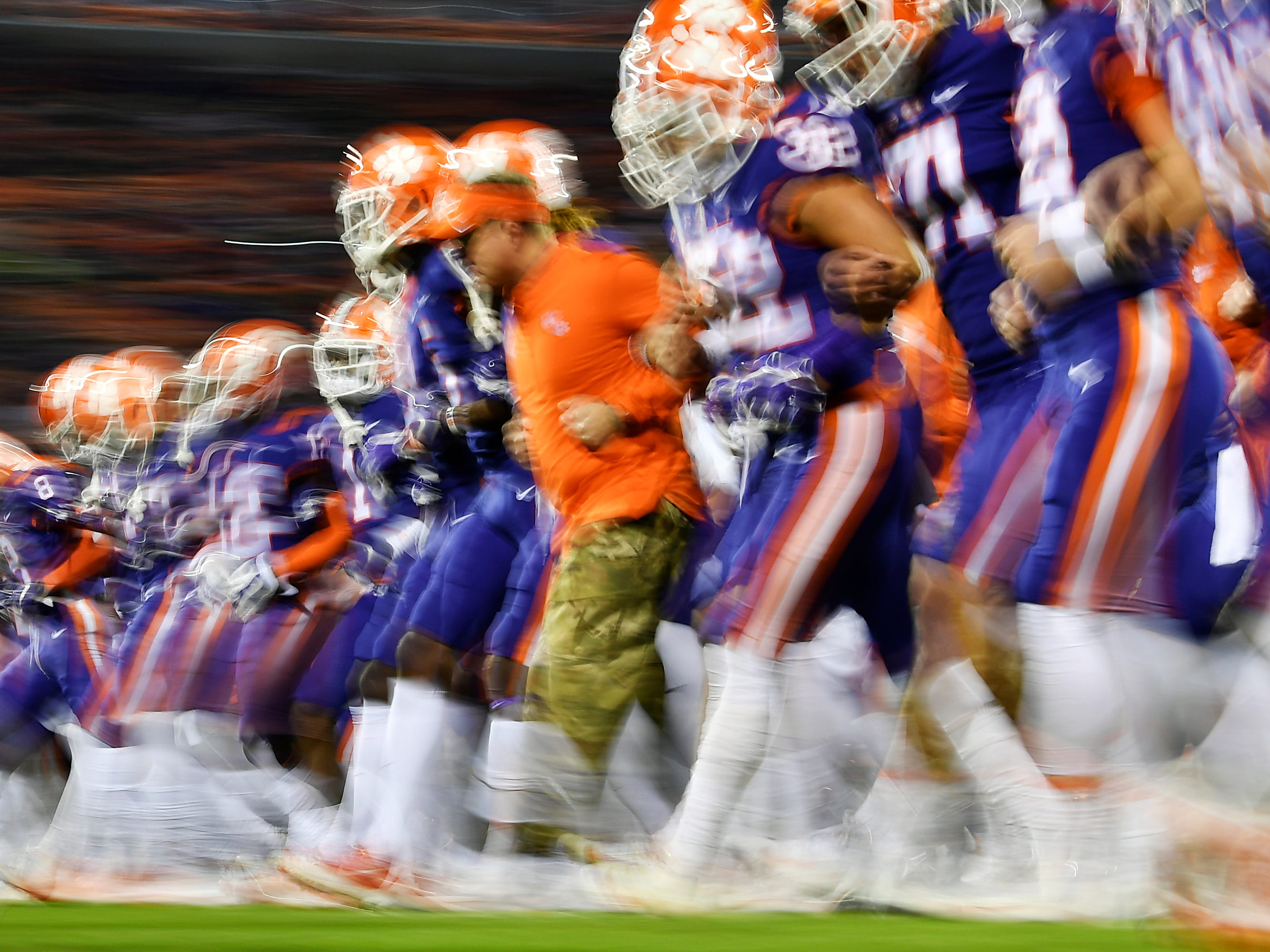 "The Clemson Tigers link arms and walk toward their end zone for their traditional ""face off"" prior to their football game against the Duke Blue Devils at Clemson Memorial Stadium on November 17, 2018 in Clemson, South Carolina."