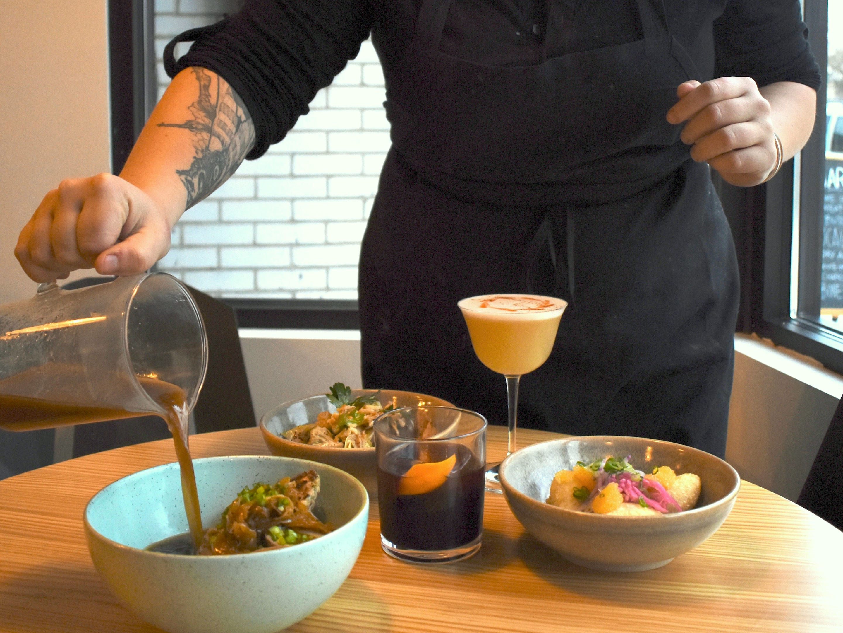 "Executive Chef / Partner Sarah Welch pours a rich pork and shrimp bone broth over shrimp dumplings for a dish called ""Noodles & Broth"" which features a rotating list of proteins, veggies and noodles."