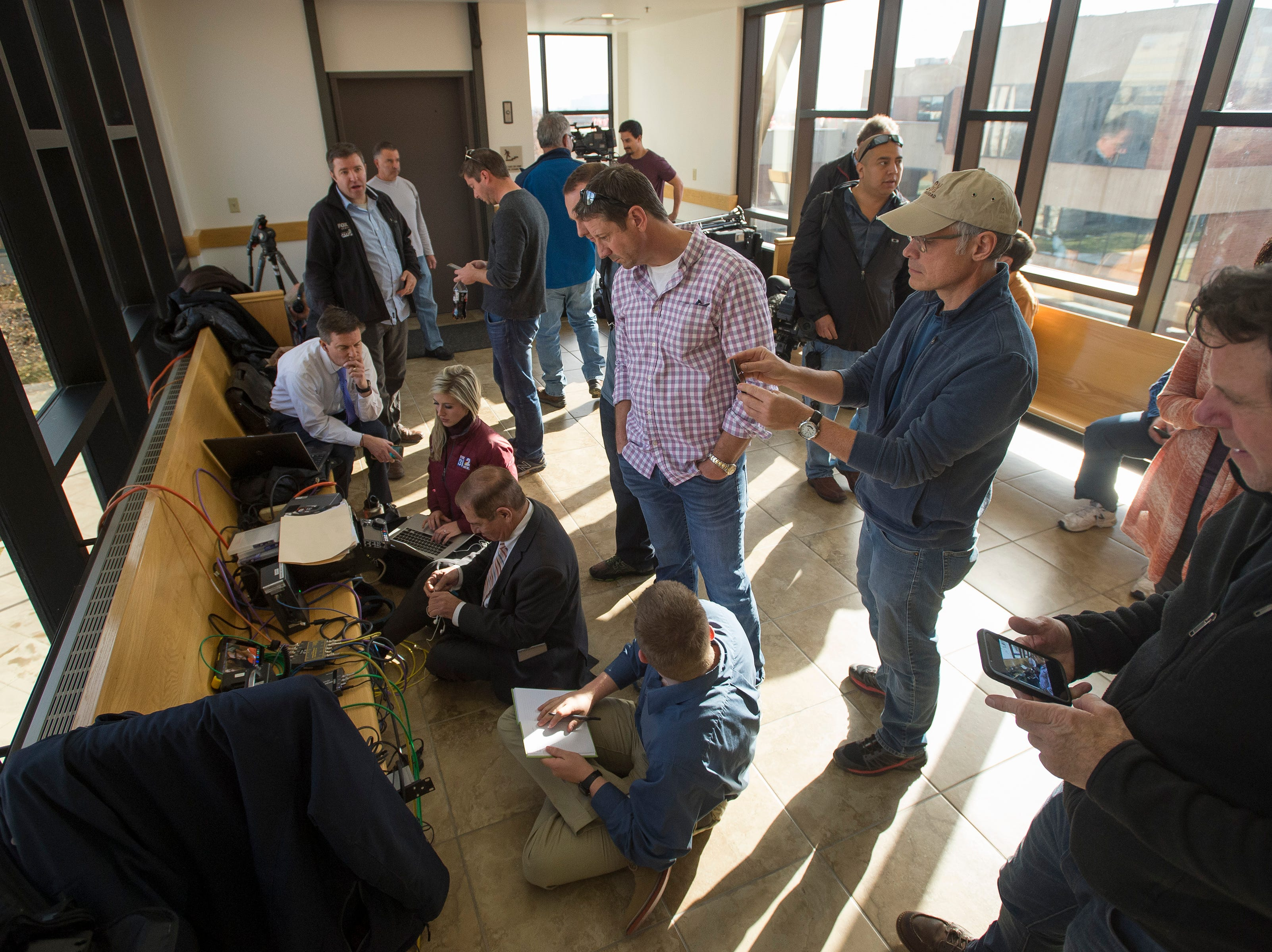 Members with various media outlets gather around a live feed from the courtroom during the sentencing of Christopher Watts for the murder of his pregnant wife Shanann, and two daughters Bella, 4, and Celeste, 3,on Monday, Nov. 19, 2018, at the Weld County courthouse in Greeley, Colo.