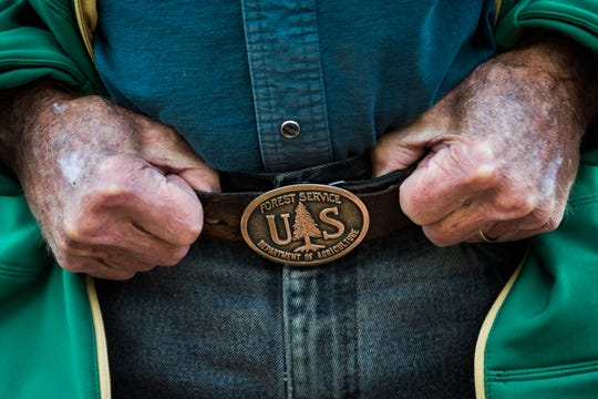 John Windsor shows his United States Forest Service belt buckles on Friday, Nov. 16, 2018, at Windsors' Christmas Trees in Windsor, Colo.