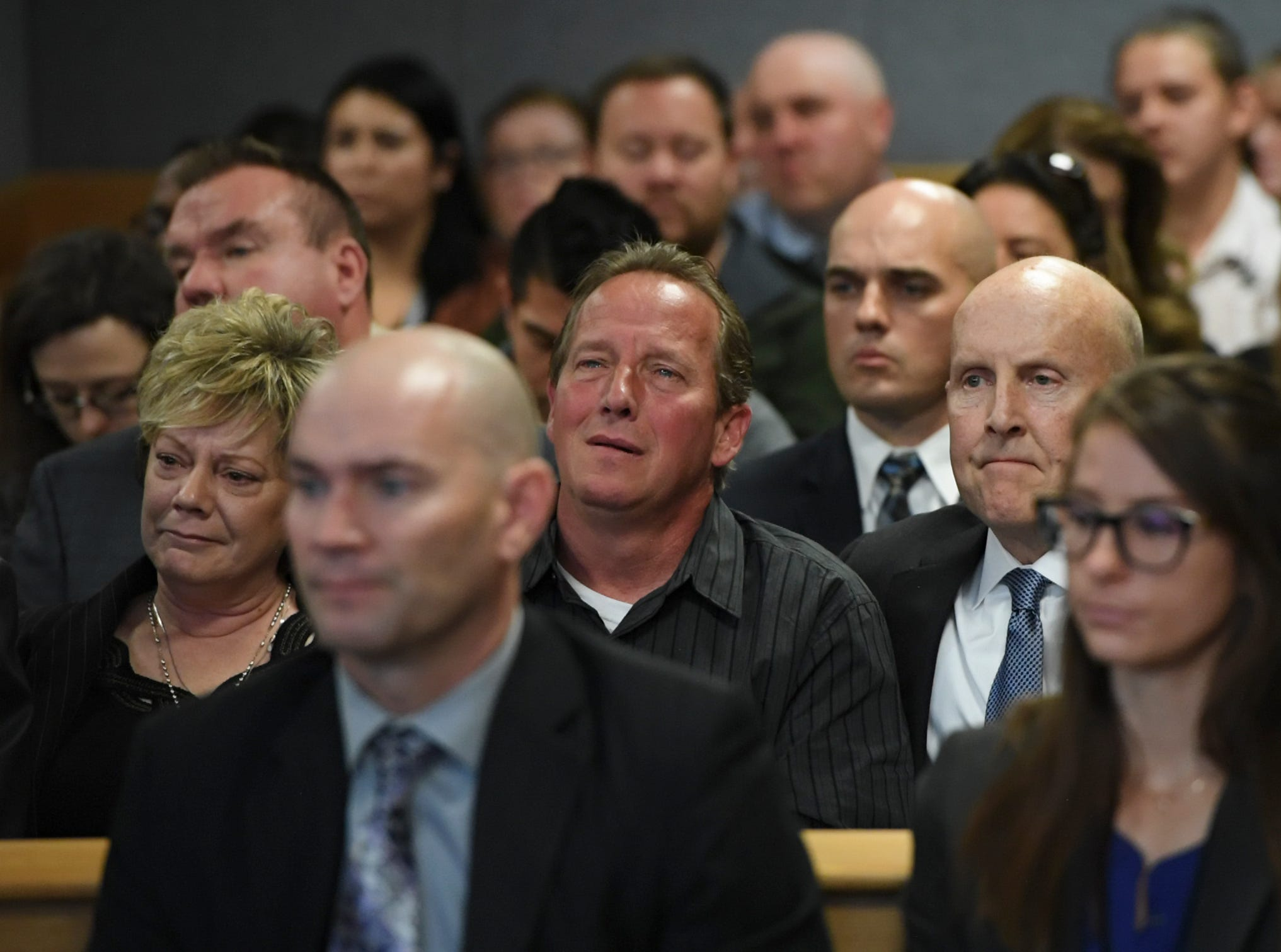 Frank Rzucek, the father of Shanann Watts, center, looks as the judge talks during the sentencing at the Weld County Courthouse on Monday, Nov. 19, 2018 in Greeley, Colo. Christopher Watts received three consecutive life sentences without a chance at parole on Monday, nearly two weeks after pleading guilty to avoid the death penalty. (RJ Sangosti/The Denver Post via AP, Pool)