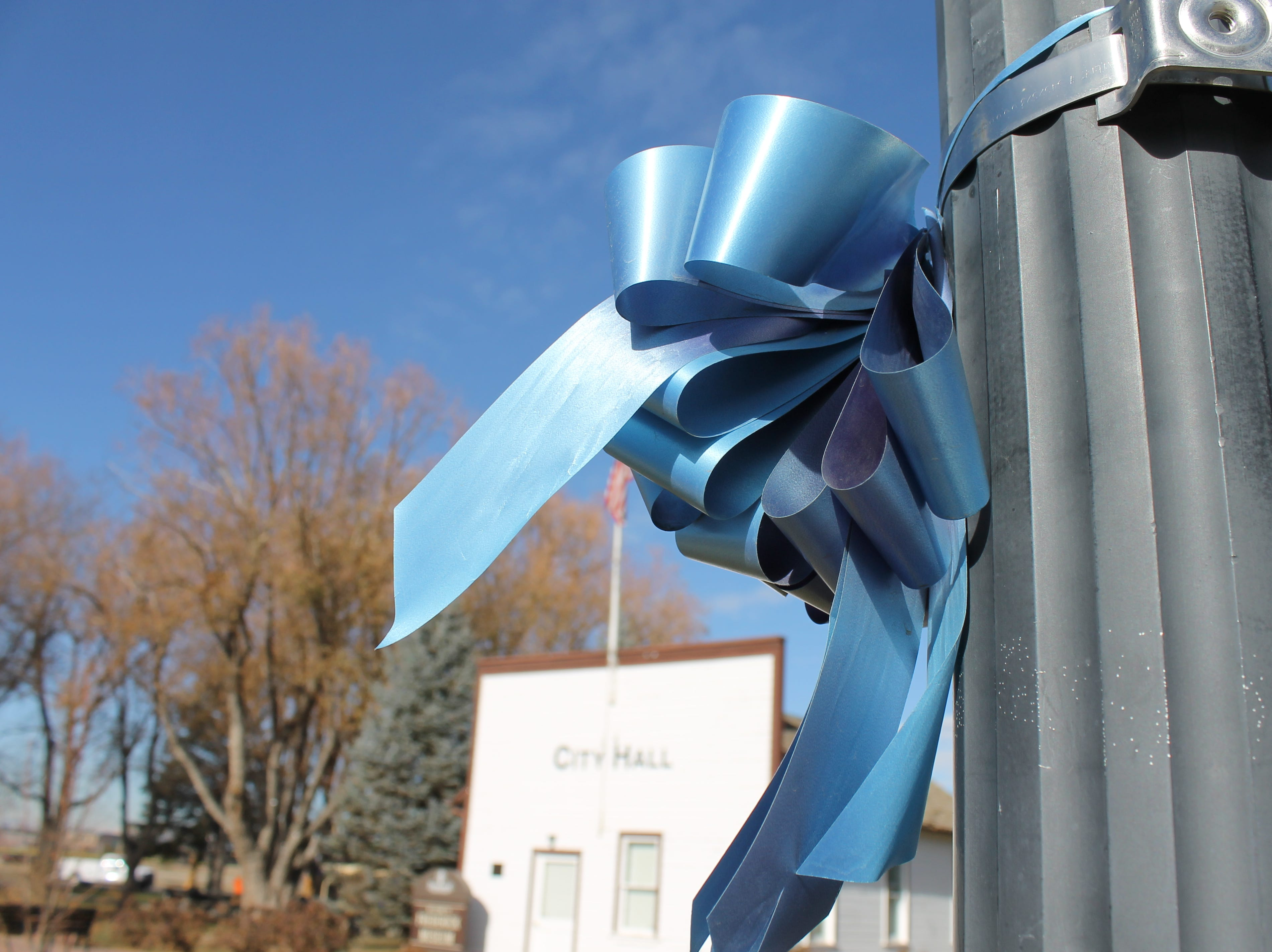 A faded ribbon hangs on a street lamp outside the Town of Frederick's City Hall Monday. Angela Wilson, the town's event coordinator, handed ribbons out in September to honor Shanann Watts and her two young daughters, Bella and Celeste. Some ribbons remain.
