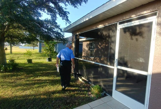 Cape Coral Police Department volunteer Roger Novak completes a security check on a home where the owner was away for four days.