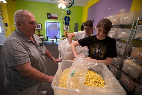 Kimberly Richards and Patrick Rohrbaugh prepare a large tin of assorted popcorn for Tom Mathison, of North Fort Myers at Wild About Popcorn. Mathison is a regular customer and often brings popcorn to local veterans at his local VFW facility.
