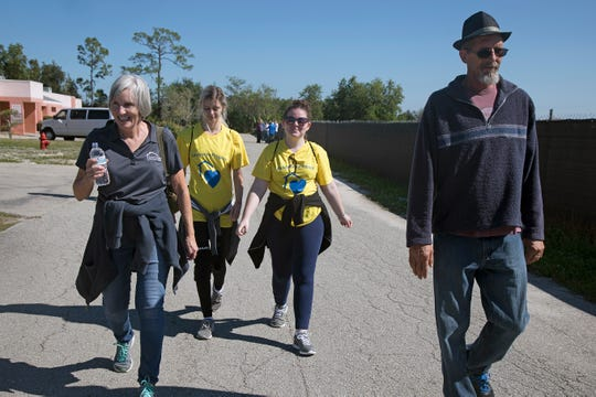 Lee County Homeless Coalition director Janet Bartos (left) hoofs it to a bus stop from the Bob Janes Triage Center during Saturday's Homeless Challenge. With her from left: FGCU students Ashley Williams and April Borden, and Jeff Meyers.