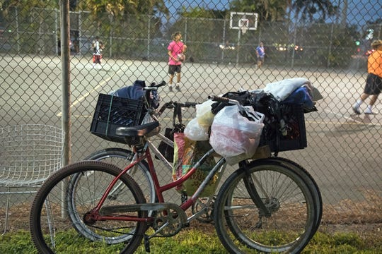 The bikes of the homeless lean against a fence at Lions Park where a free Thanksgiving dinner is being served on Saturday. Along with the obvious hazards of homelessness, motorists kill more bicyclists and pedestrians in Lee County than any other county in the state of Florida, according to county homeless outreach worker Matt Wallace.