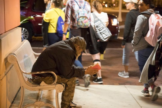 Homeless Challenge participants pass a homeless man resting on a bench in the heart of downtown Fort Myers on Saturday night. The annual event organized by the Lee County Homeless Coalition invites people to spend a long day walking in a homeless person's shoes.