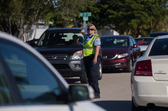 Cape Coral Police department volunteer Doreen Robertson helps re-route traffic after officers responded to a shots fired incident at an apartment complex off Santa Barbara Blvd. near the intersection of SW 29th Terrace on October 29, 2018.