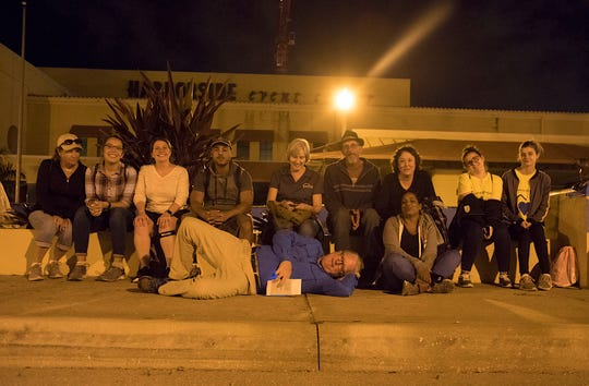 A pooched but cheerful Homeless Challenge team rests a spell on a wall in Centennial Park in downtown Fort Myers on Saturday night.