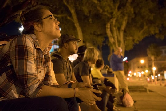 Sasha Villalobos, a public health major at FGCU, takes in the night scene at Centennial Park in downtown Fort Myers during Saturday's Homeless Challenge.