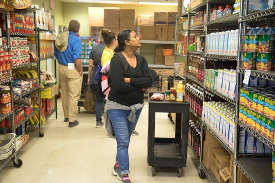 Homeless Challenge participant Sasha Ammersingh checks out the food pantry shelves at Community Cooperative, a soup-to-nuts soup kitchen in Fort Myers where people can connect with other services besides a free meal.