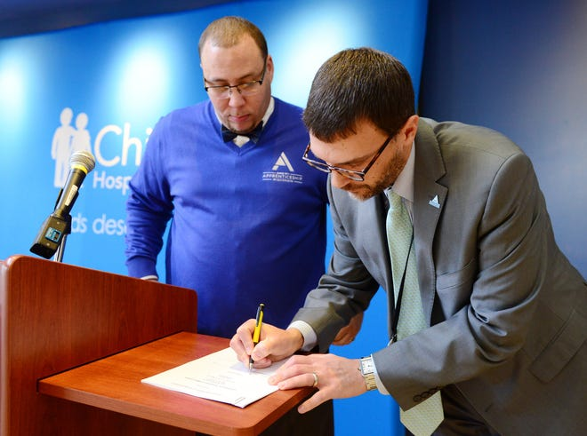 DWD's Bureau of Apprenticeship Standard Chief of Field Operations and Children's Hospital of Wisconsin's Vice President of Health Management Operations sign the Apprenticeship Standards for the first IT Data Analyst Apprenticeship.