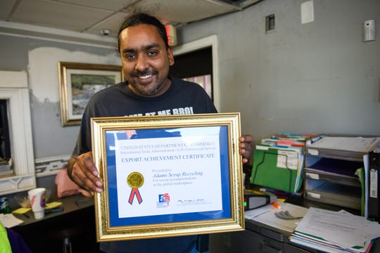 Rajesh Desor holds a certificate from the United States Department of Commerce at Adams Scrap Recycling received on Monday, Nov. 19, 2018.