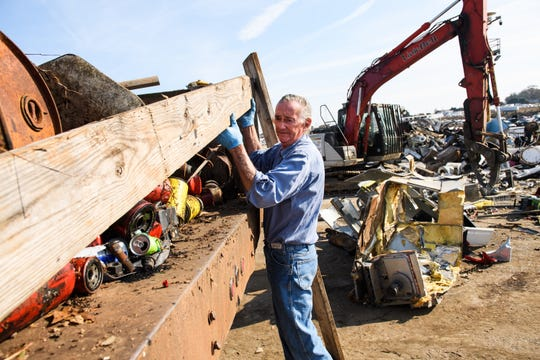 Earl Gentry lifts planks of wood from the back of his truck before dumping scrap metal off at Adams Scrap Recycling on Monday, Nov. 19, 2018.