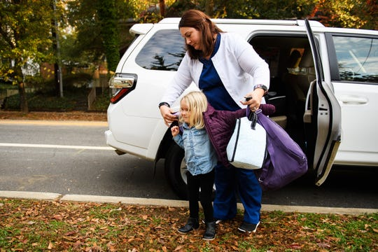 Kate Richardson helps her 3-year-old daughter Olivia put on her jacket before dropping her off at the Haynsworth School on Monday, Nov. 19, 2018.