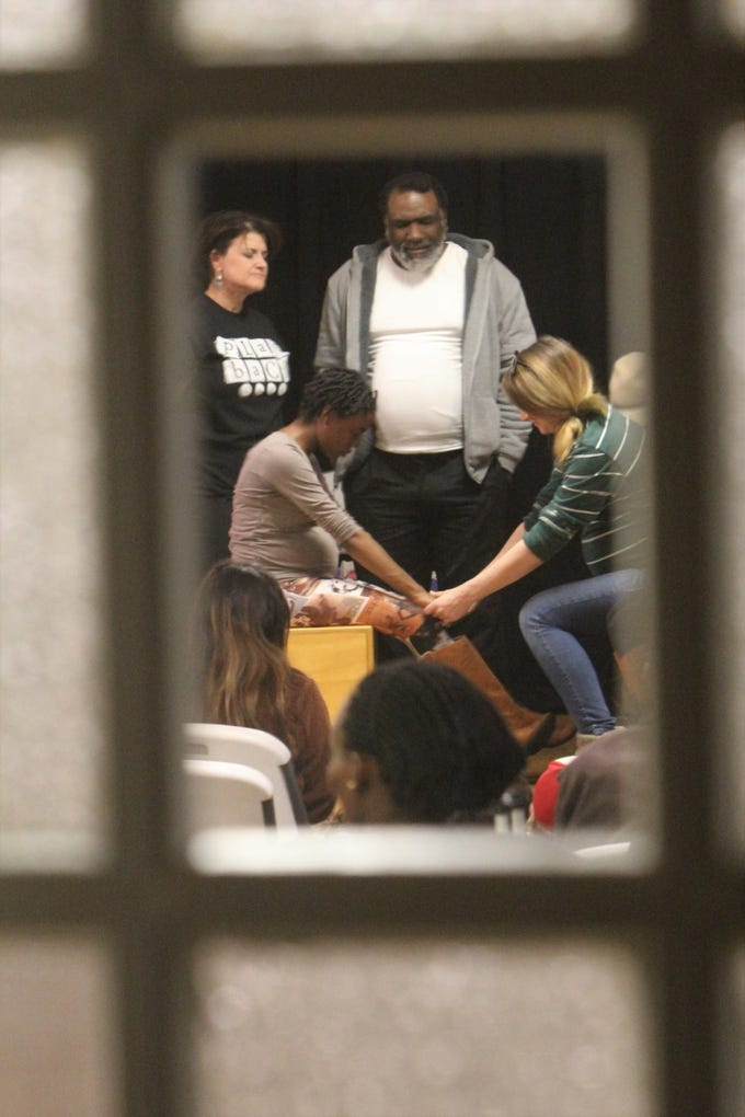 A group of performers stop acting to pray with Jori Green, left sitting. She has been sober for about two and a half months and asked for the prayers.