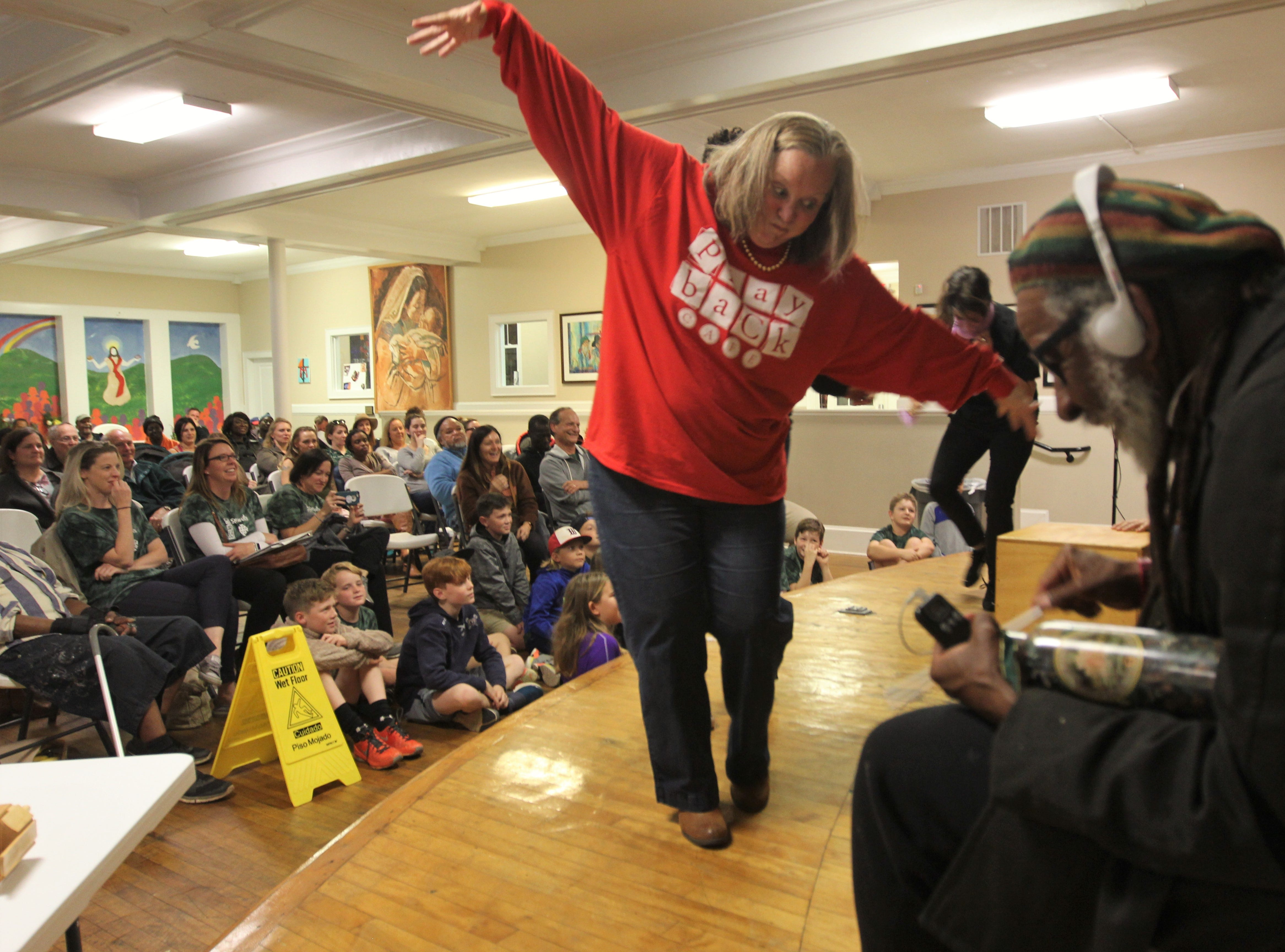Julia Turlington plays as a Thanksgiving parade balloon while recreating a story from an audience member at Triune Mercy Center.