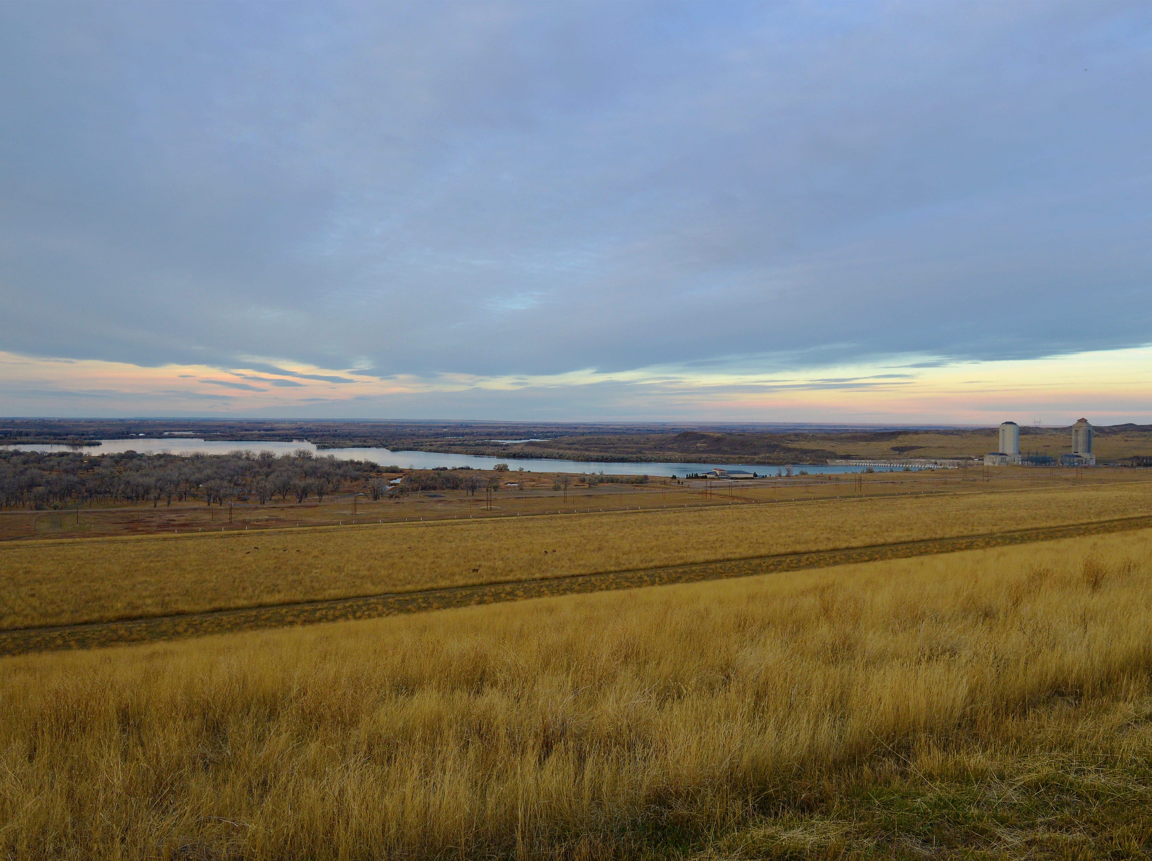 The Missouri River continues on its journey east below the Fort Peck Dam and powerhouses.
