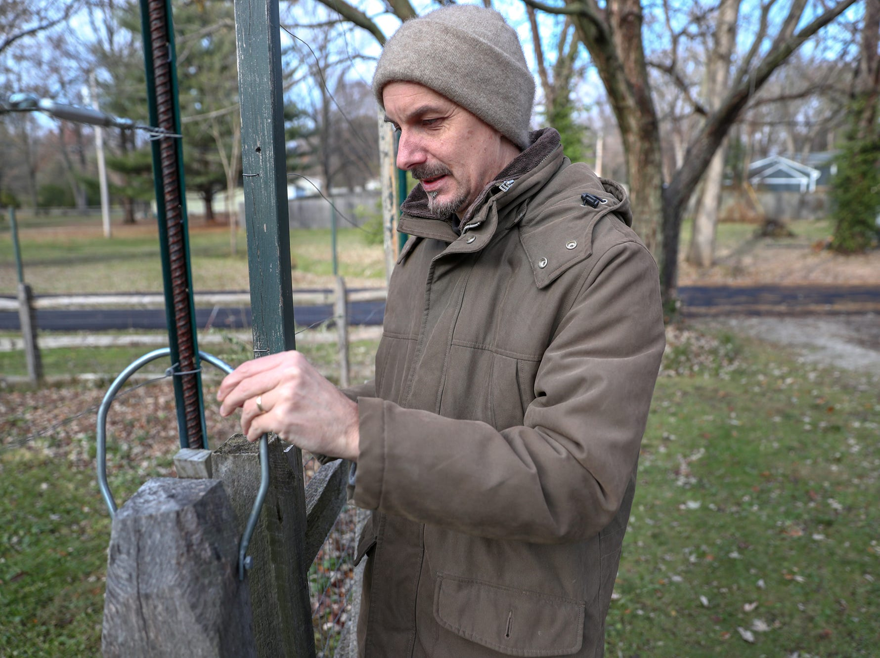 Adam Schwarz lifts the latch on a gate that leads to his three-acre yard in Carmel, Ind., on Friday, Nov. 16, 2018.