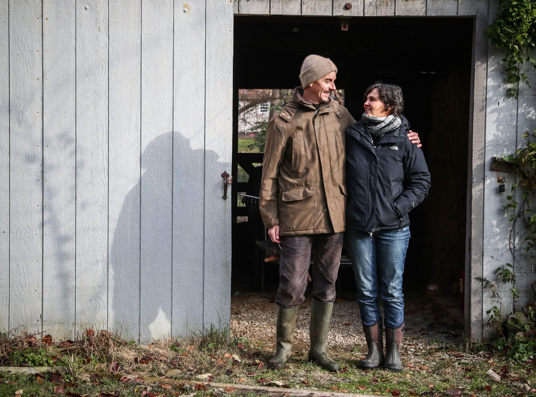 Adam and Emmanuelle Schwarz share a laugh while posing for a portrait in front of a small barn on their property in Carmel, Ind., on Friday, Nov. 16, 2018.