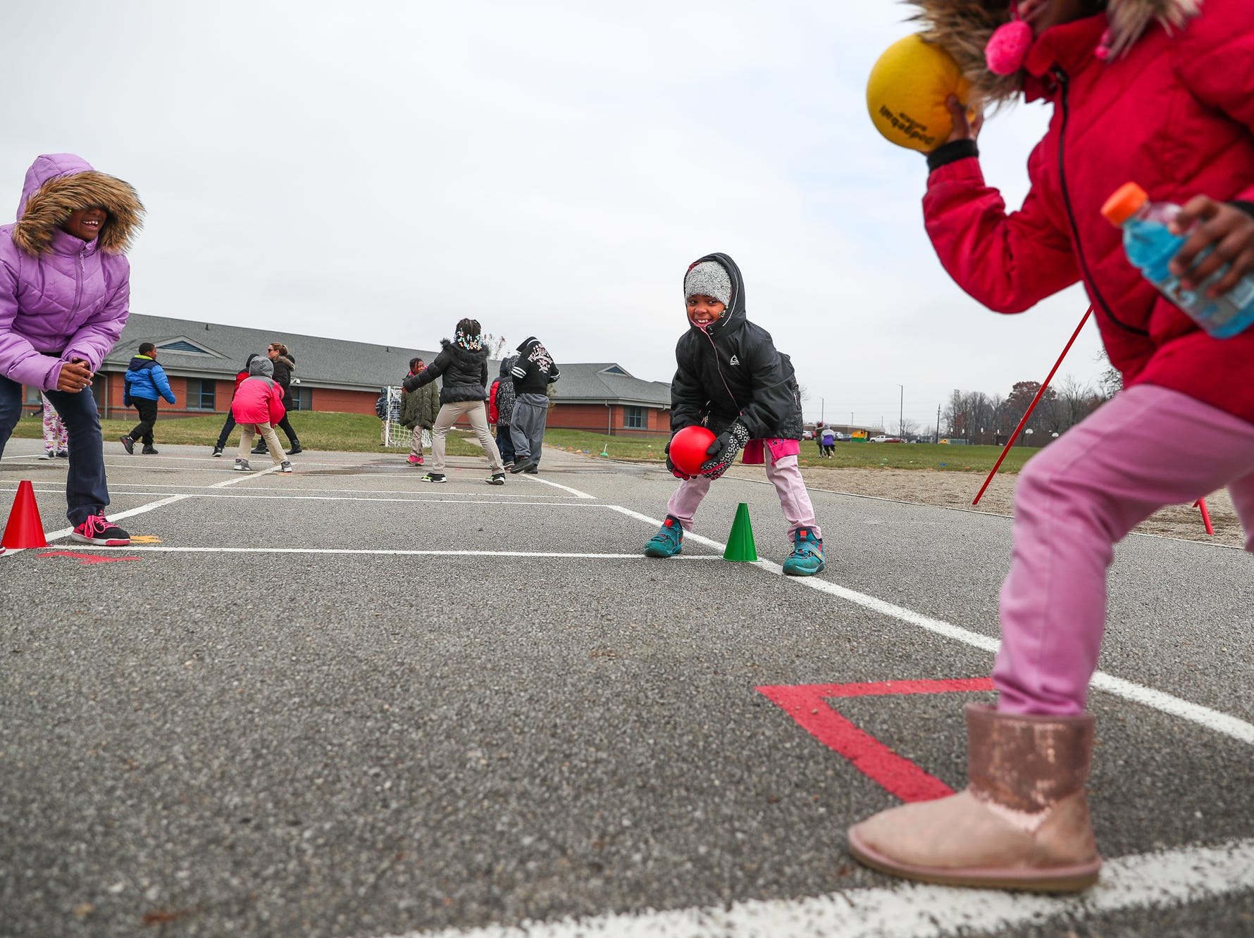 Aminah Brounson (middle), 8, eyes the cone of a fellow Gnome Guardian player during recess at Sunny Heights Elementary School on Friday, Nov. 16, 2018.