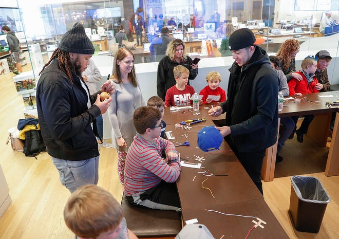 Colts defensive end Jabaal Sheard (left) and Colts punter Rigoberto Sanchez sign autographs for kids before to playing activities with them. About 20 children from the A Kid Again program, who are fighting life-threatening illnesses, gathered at the Microsoft store at The Fashion Mall on Monday, Nov. 19, 2018.