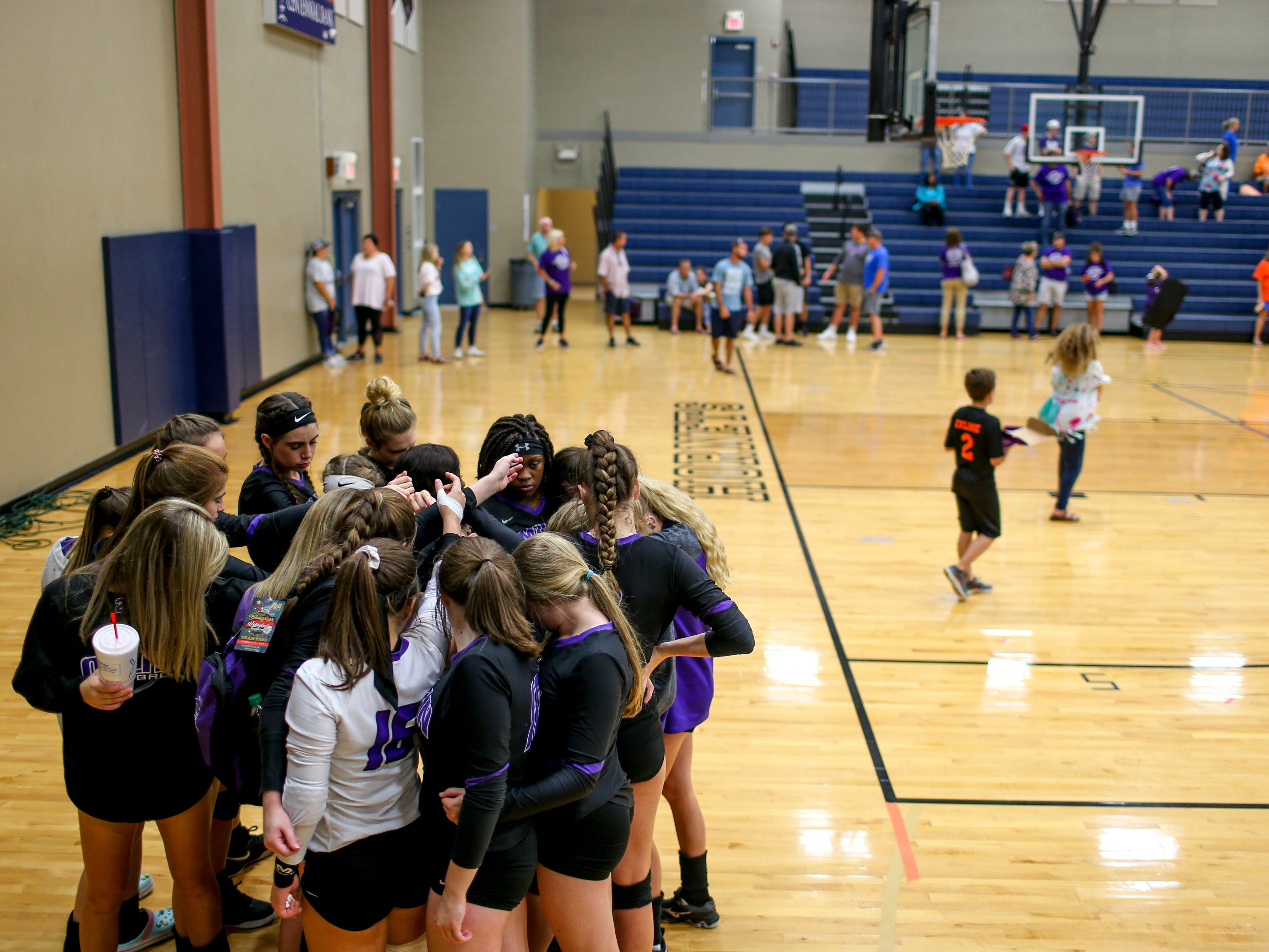 Bailee Graves (16) puts her arm into the mix of players during a huddle before a TSSAA volleyball game between Milan High School and South Gibson County at South Gibson County High School in Medina, Tenn., on Thursday, Sept. 13, 2018.