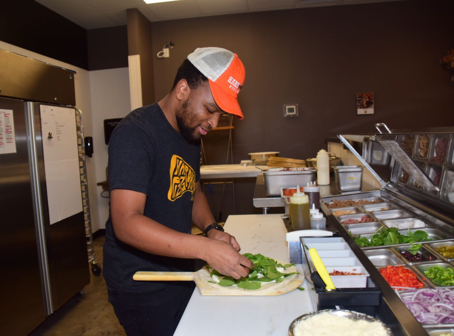 Quanelo Evans prepares an Iron Mike pizza. It features spinach, fresh mozzarella, and shaved parmesan cheese at Hard Knox Pizza.