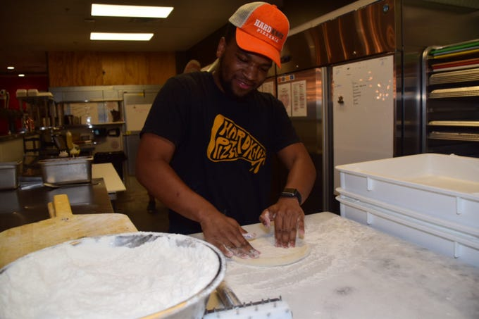 Quanelo Evans spreads dough getting ready to toss it at Hard Knox Pizza.