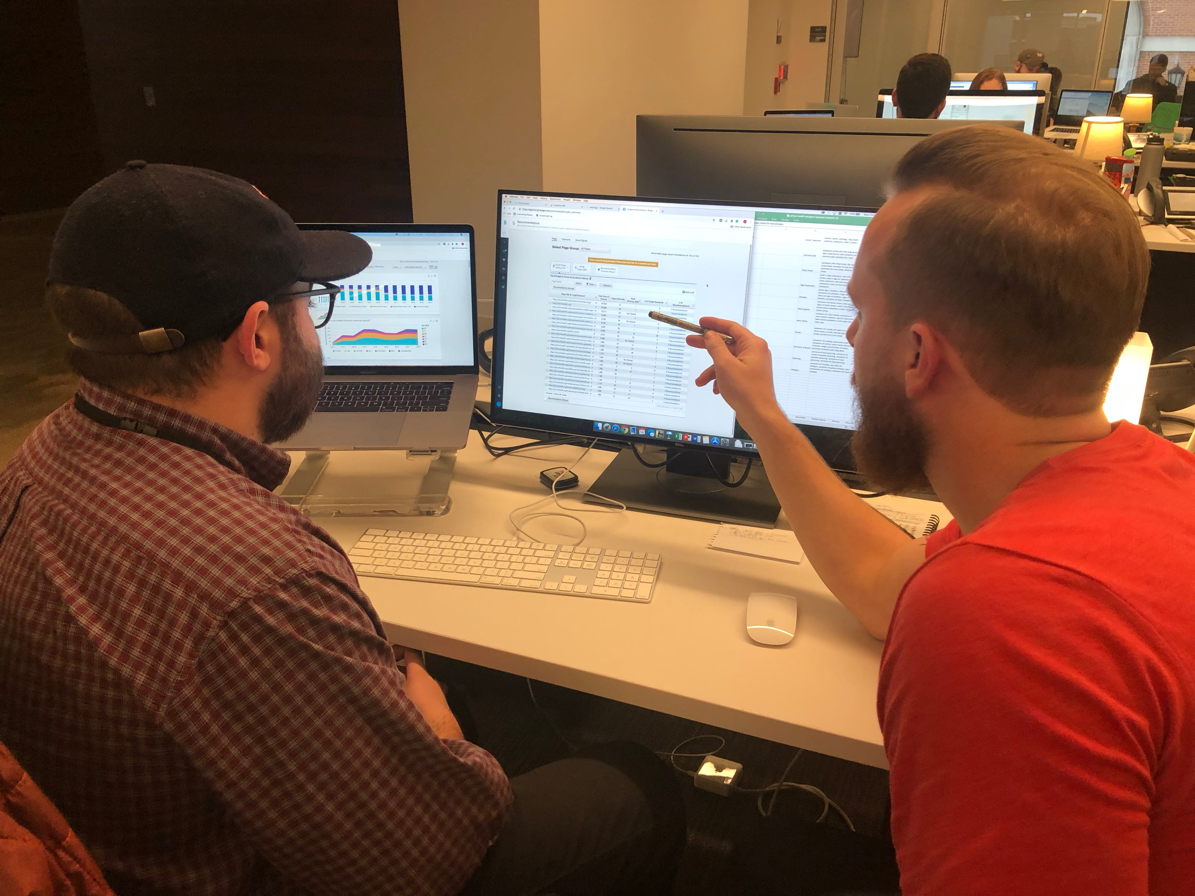 Cole Mauer, director of content SEO at Tombras, right, mentors new hire, Jefferson Douglas, SEO assistant, on how to use a state of the art A.I. powered SEO platform.