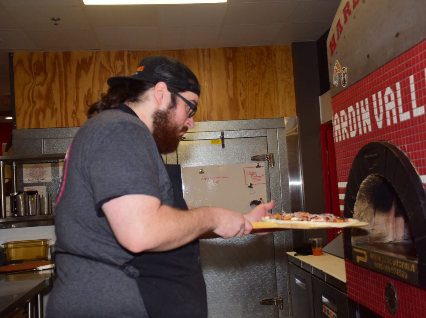 Jimmy Swartz carefully places a pepperoni pizza in the 750 degree wood fired oven at Hard Knox Pizza.