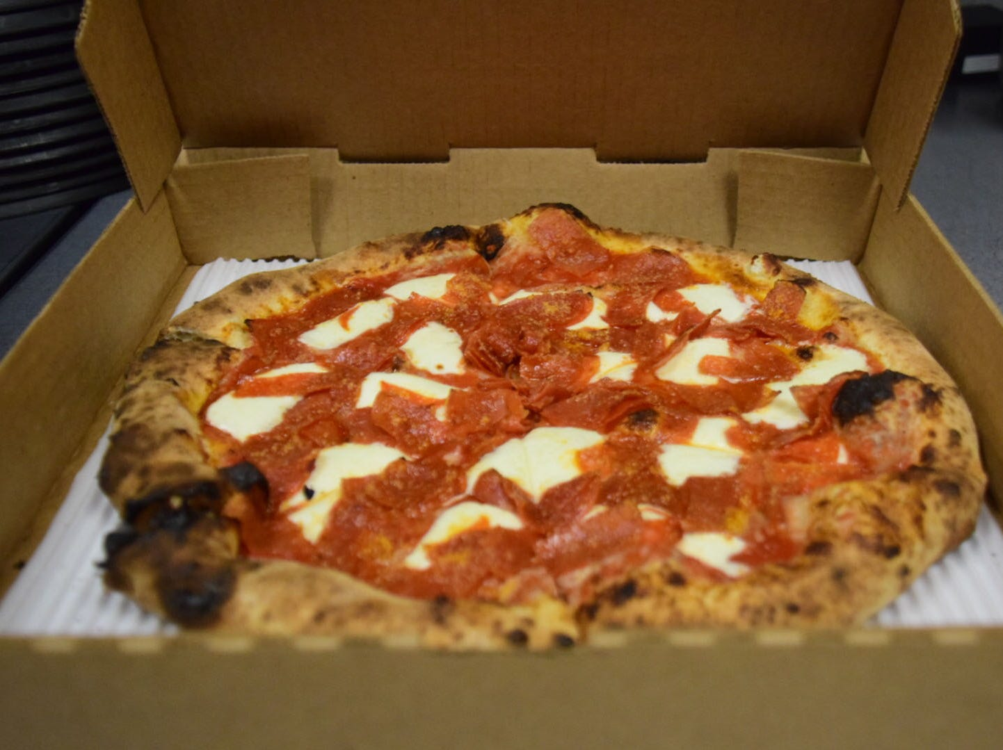 A freshly baked pepperoni pizza is ready to go carry out at Hard Knox Pizza.