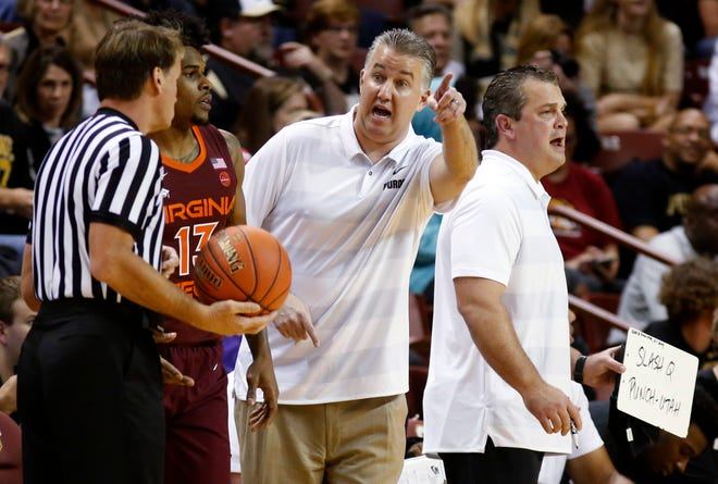 Purdue coach Matt Painter, center, talks with an official during the first half of the team's NCAA college basketball game against Virginia Tech at the Charleston Classic in Charleston, S.C., Sunday, Nov. 18, 2018.