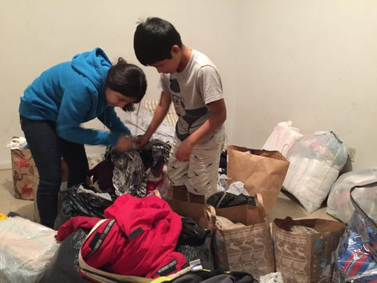 Sheila Vargas, 11, and her brother Nicholas Vargas, 10, sort through donated clothes Saturday night in an apartment provided by their family's landlord following a fire on Friday that destroyed their home.
