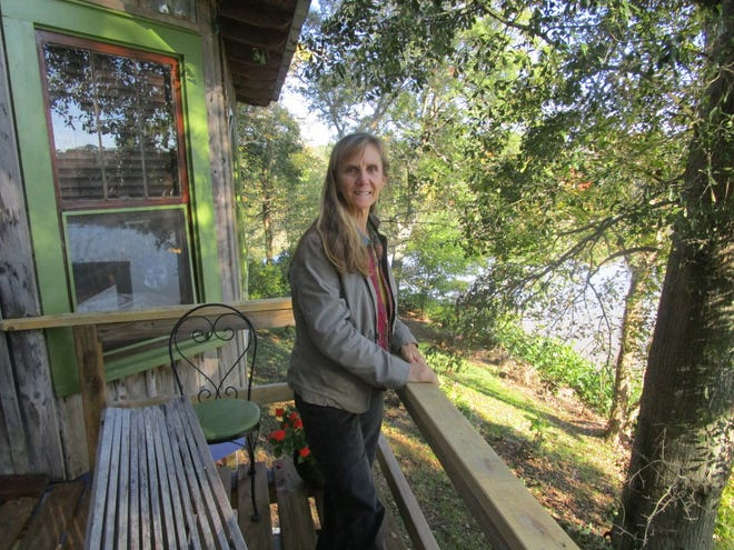 Kathleen Whitehurst, artist, relaxes on the deck of her home over looking Hidden Hills lake.