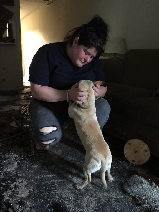 Casey Ambros embraces her dog, Whittey, in her apartment the day after they were rescued from a fire there.
