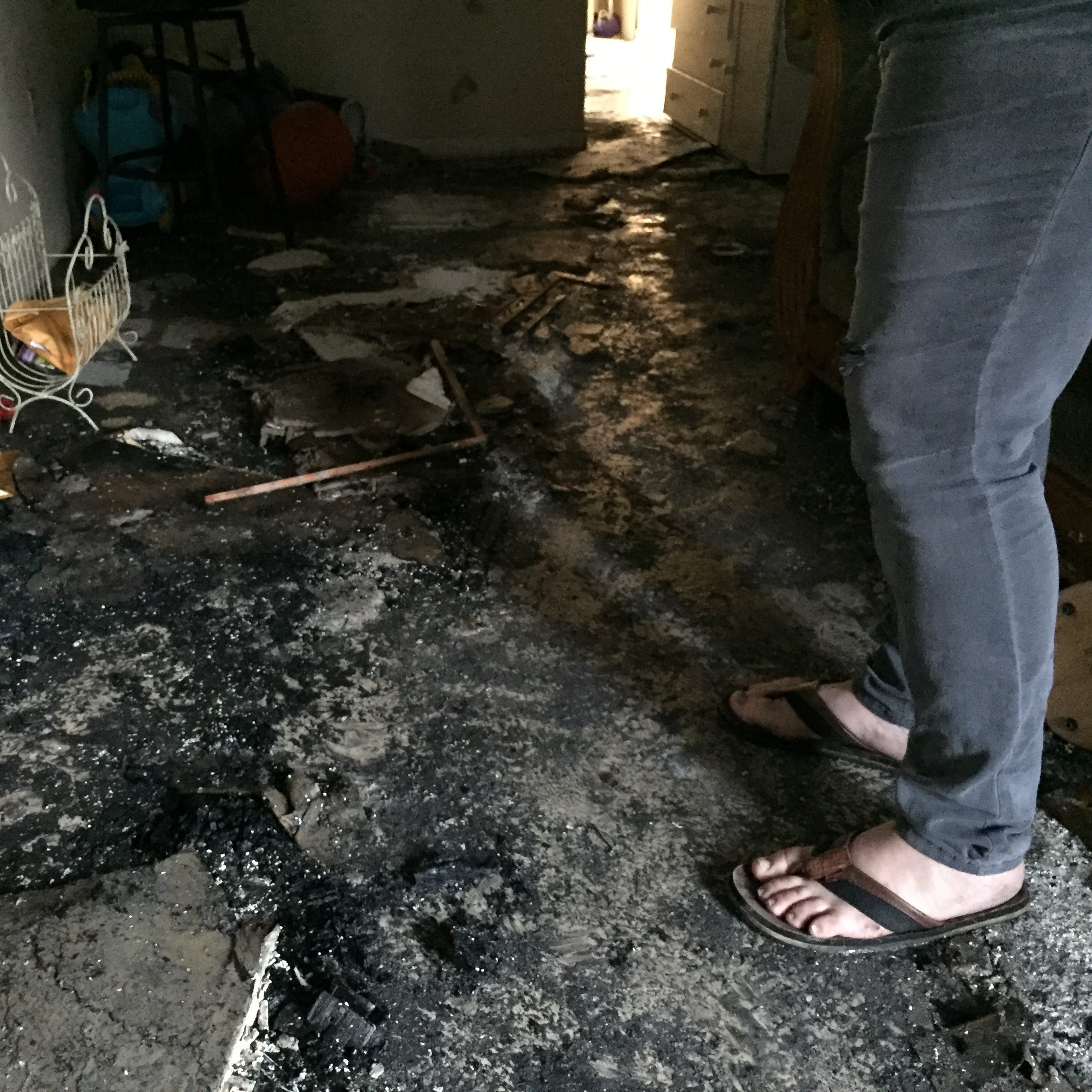 Casey Ambros walks through her charred apartment after salvaging the last of what she could: food from the freezer. She is one of 22 people displaced by the Friday morning fire.