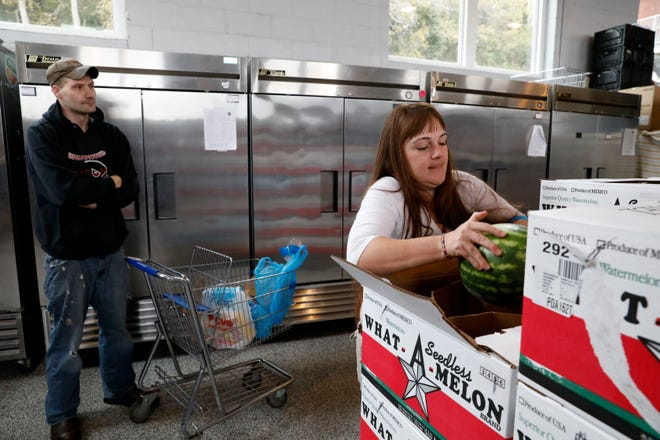 Jennifer Tope grabs a watermelon for Richard Hooker, of Lancaster, Oct. 30, 2018, at the Lancaster-Fairfield Community Action Agency food pantry in Lancaster.