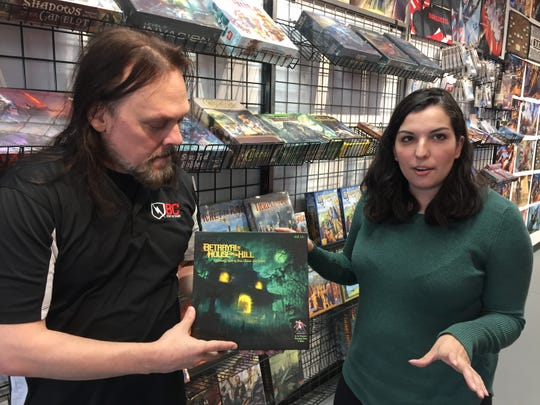 """BC Comix and Games managers Joslyn Lambaria and Chris Kelley discuss """"Betrayal at House on the Hill"""" at the store Monday, Nov. 19, 2018. They expect the board game to be a popular seller this holiday shopping season."""