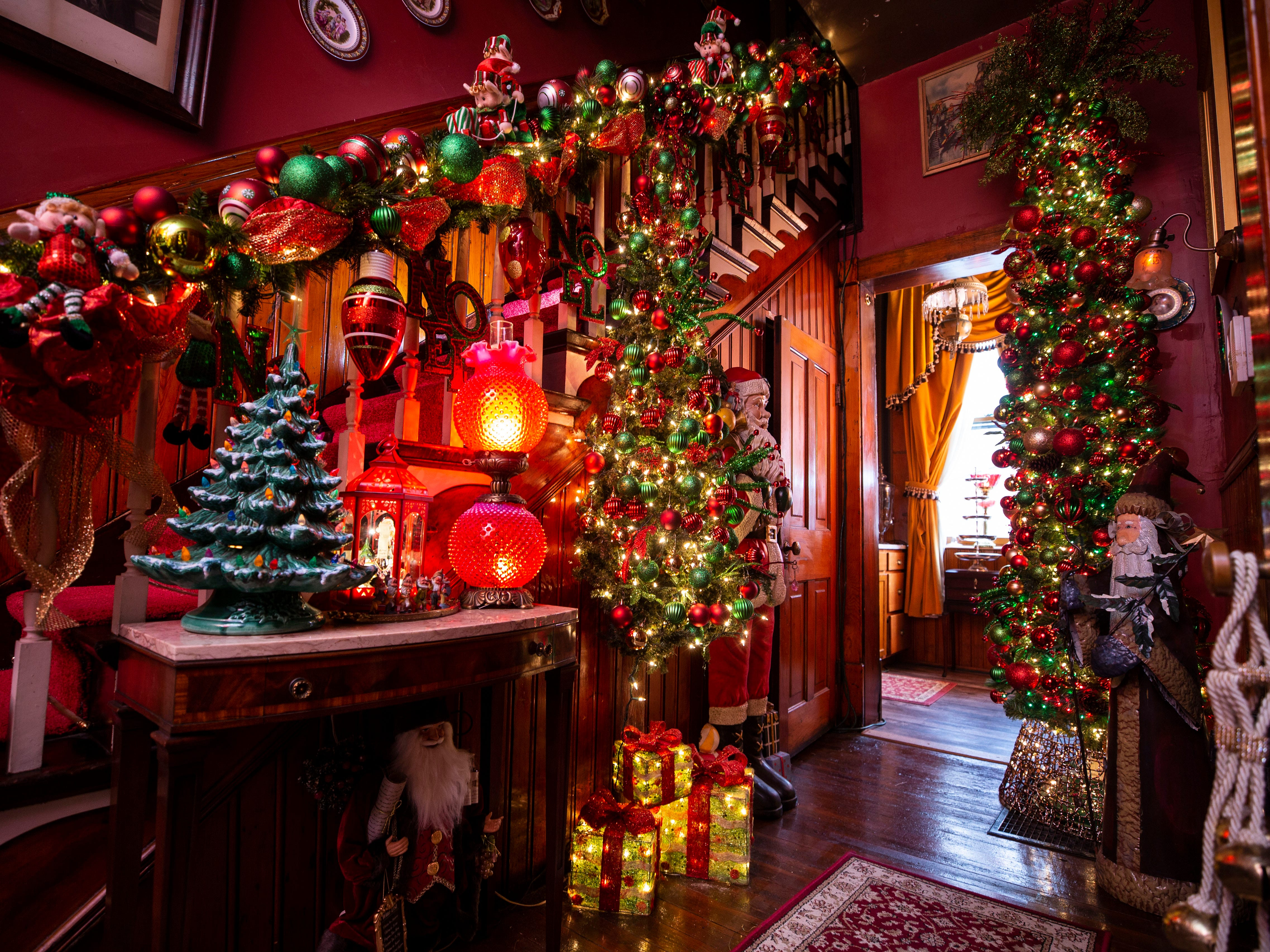 """""""If it's good craftsmanship, and it's pretty it goes well with these homes,"""" said David Brown. The second staircase has hundreds of ornaments and Christmas trees decorate the small hallway that leads to the bar area. The Victorian-era, three-story home is part of the Old Louisville Holiday Home Tour."""