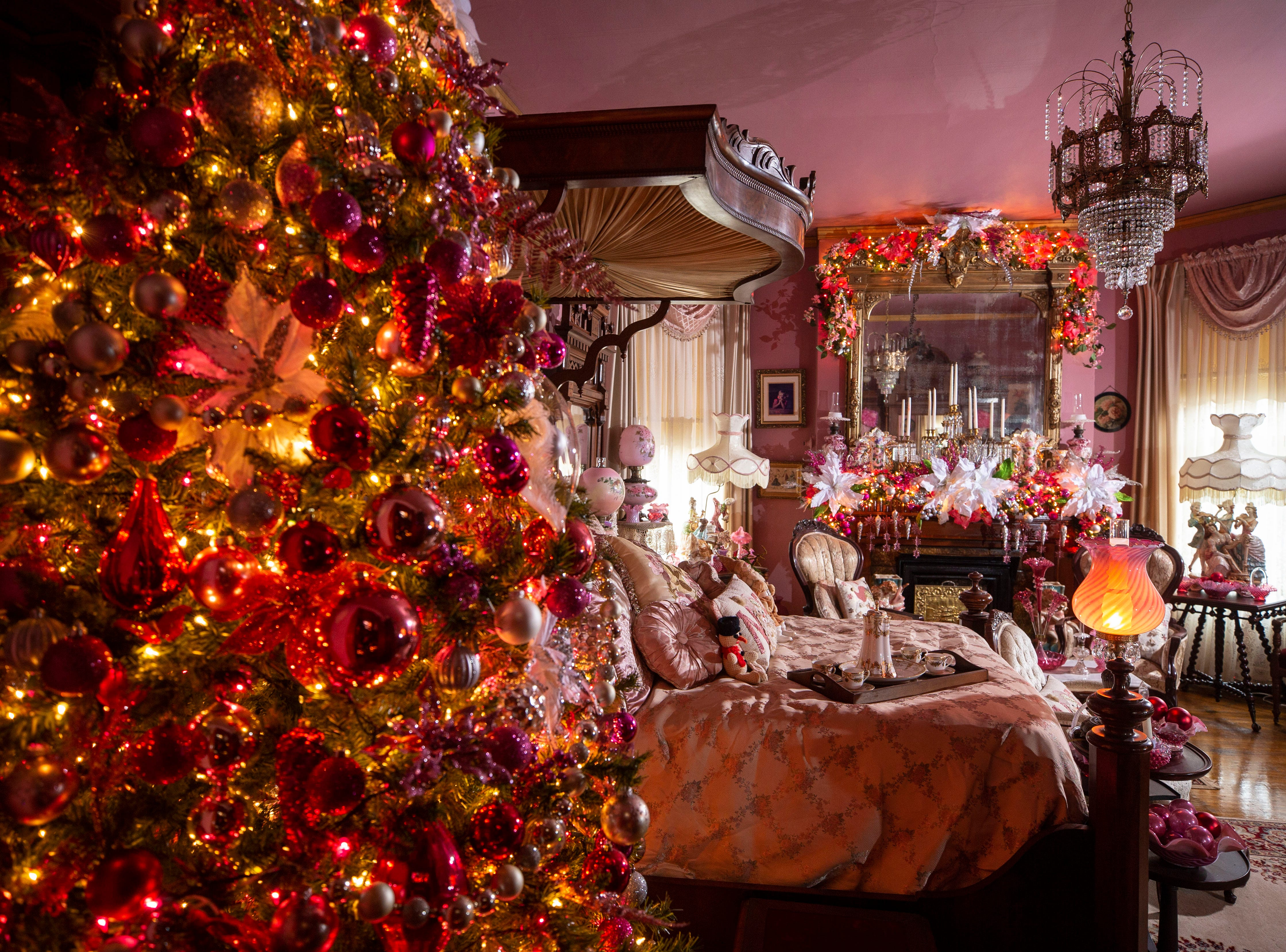 This second floor bedroom features a pink-themed Holiday decorations and tree. Through years of hunting at auctions, David Brown collected hundreds of period-correct antiques.