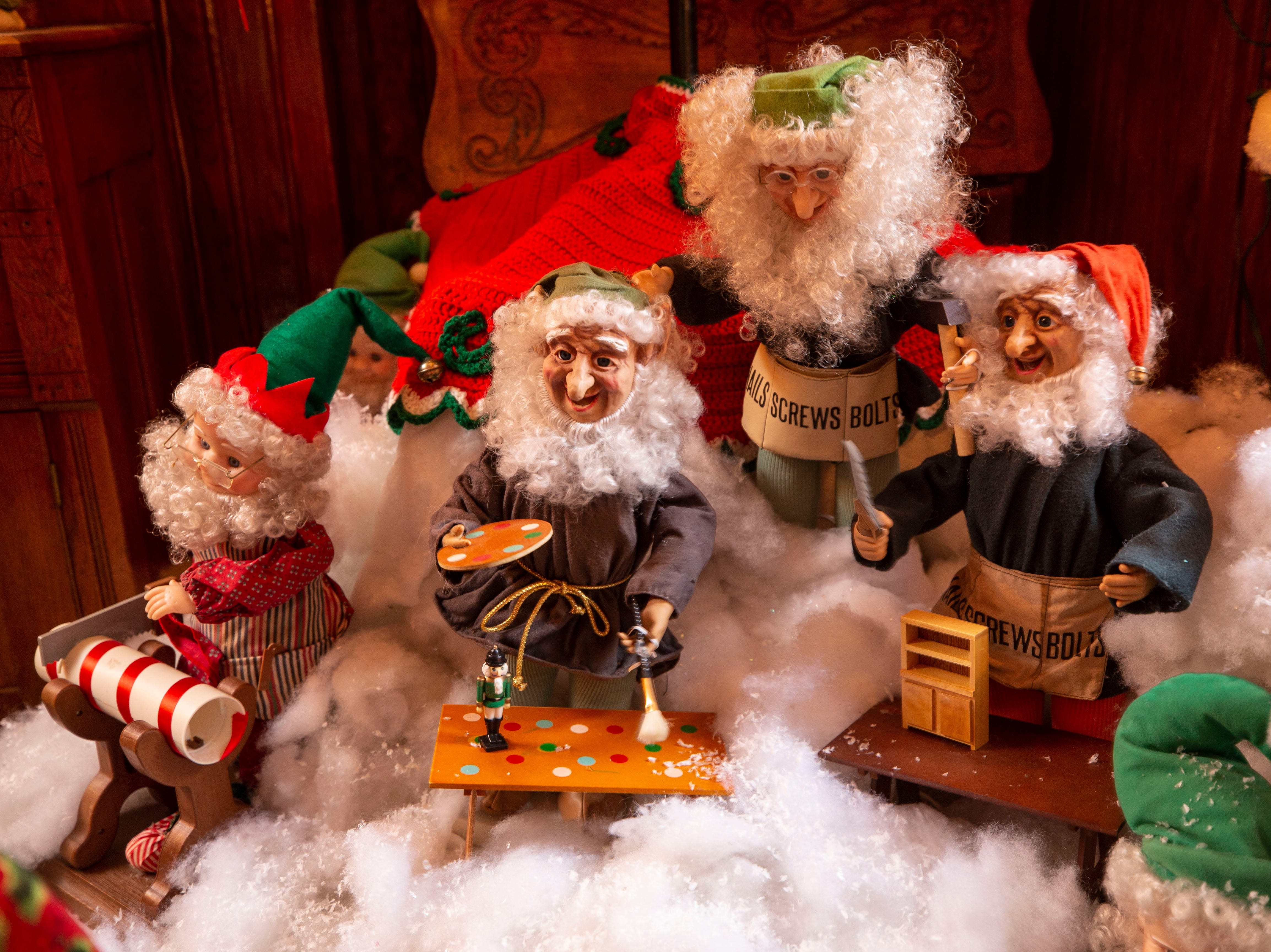 These mechanized elves sit on a bed of cotton snow underneath a Christmas tree in the kitchen. Every room in the home has a tree.